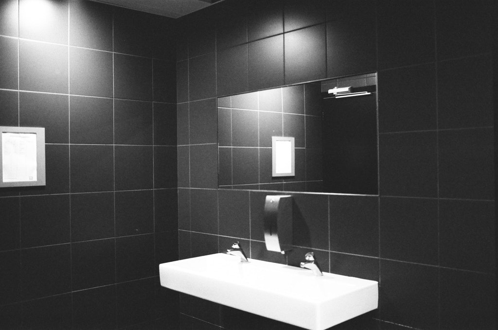 bathroom sink and mirror with black tiles