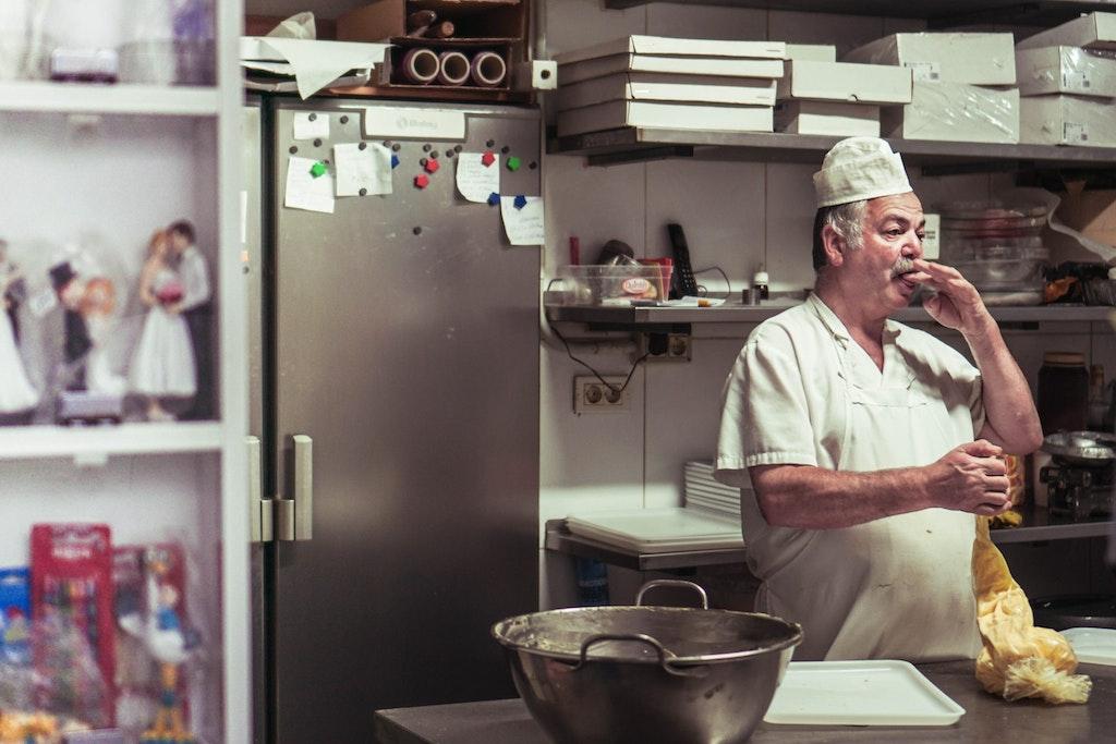 baker tasting his dough in kitchen